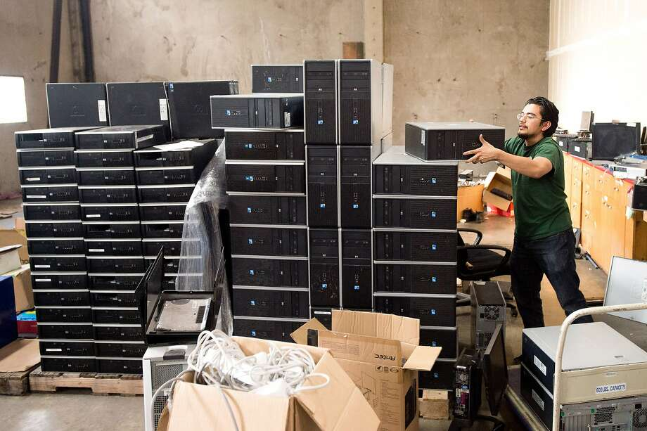 Kemish Rosales moves desktop computers at the Oakland Technology Exchange, which donates them to needy families. Photo: Noah Berger, Special To The Chronicle