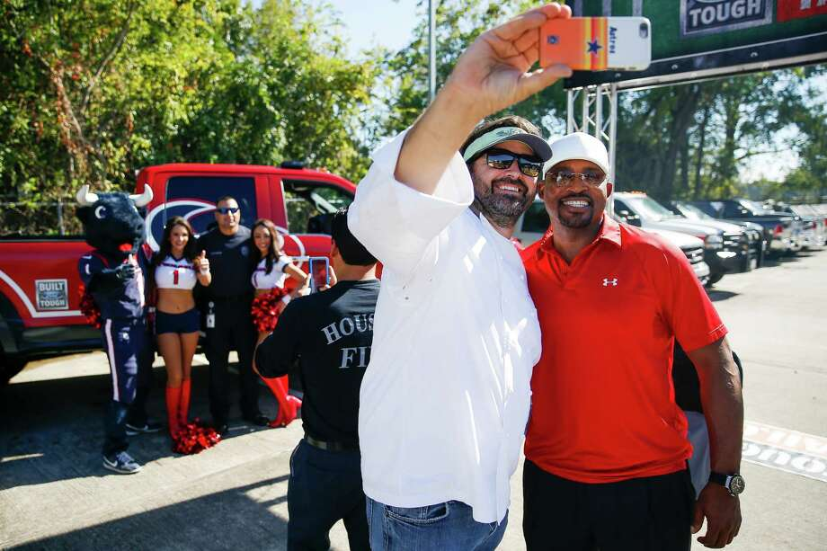 Chef Bryan Caswell, left, takes a selfie with former NFL player Andre Ware as he cooks for Houston firefighters at the Built Ford Tough Toughest Tailgate at Station 11 Wednesday, Nov. 23, 2016 in Houston. Photo: Michael Ciaglo, Houston Chronicle / © 2016  Houston Chronicle