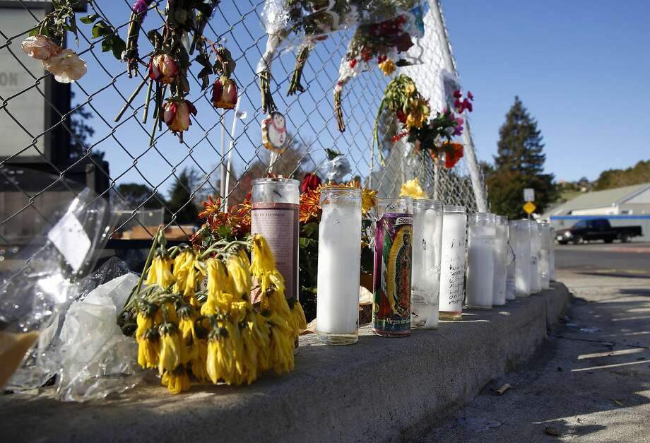 A memorial of flowers and candles are arranged at Appian Way and Garden Road in El Sobrante, Calif. on Wednesday, Nov. 23, 2016 near the spot where William Sims was slain earlier this month. One man is in custody and two others are being sought for the murder of Sims, 28, which police has labeled as a hate crime. Photo: Paul Chinn, The Chronicle