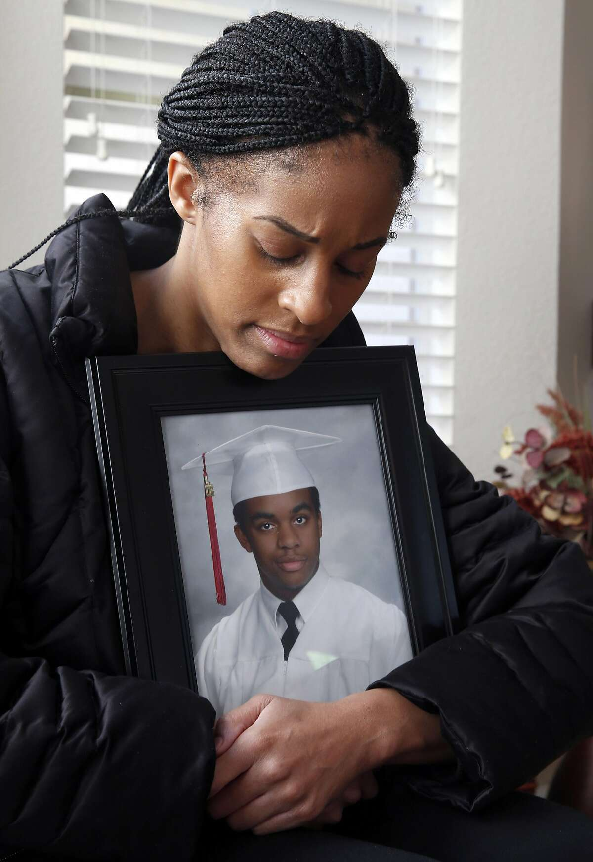 Stacey Sims clutches a portrait of her brother William Sims at her family's home in Richmond, Calif. on Wednesday, Nov. 23, 2016. One man is in custody and two others are being sought for the murder of William Sims, 28, which police has labeled as a hate crime.