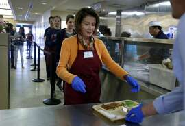 Rep. Nancy Pelosi delivers a lunch plate of pasta fagioli to guests at the St. Anthony's Foundation dining room in San Francisco, Calif. on Wednesday, Nov. 23, 2016. Volunteering during the holiday season is an annual activity for Pelosi.