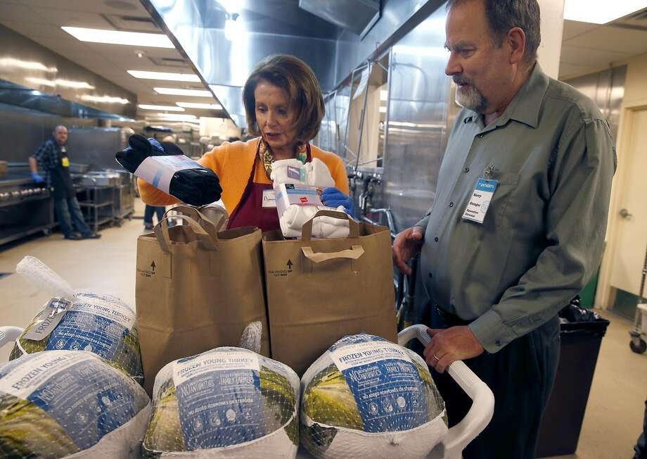 Rep. Nancy Pelosi donates several turkeys and pairs of socks to St. Anthony's Foundation executive director Barry Stenger before serving meals to guests at the dining room in San Francisco, Calif. on Wednesday, Nov. 23, 2016. Volunteering during the holiday season is an annual activity for Pelosi. Photo: Paul Chinn, The Chronicle