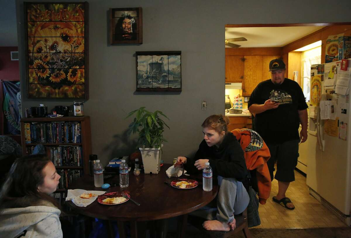 Haylie Sunderland, 18, left, and family friend Shyann De Haven, 14, eat breakfast as Sunderland's step-father Chris Phillips checks his phone in his and his wife Michele Sunderland's home Nov. 23, 2016 in Livermore, Calif. Phillips and his wife Michele Sunderland are part of a medical cannabis collective and both run medical cannabis businesses. In June Phillips' home was raided by the police and Phillips was arrested along with his brother and a few colleagues. The bail cost the group everything they had plus money they were able to raise from the community. Now Phillips and his wife face eviction because the police sent a letter to their landlord stating that there had been criminal activity in the home, says Phillips.