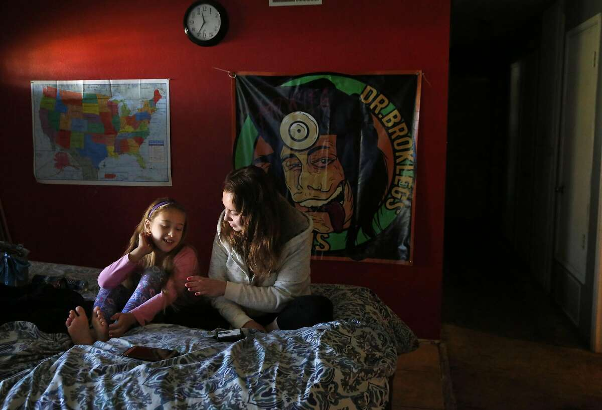Cousins Haylie Sunderland, 18, right, and Emilie Phillips, 8, chat in the living room of Sunderland's step-father Chris Phillips and her mother Michele Sunderland's home Nov. 23, 2016 in Livermore, Calif. Phillips and his wife Michele Sunderland are part of a medical cannabis collective and both run medical cannabis businesses. In June Phillips' home was raided by the police and Phillips was arrested along with his brother and a few colleagues. The bail cost the group everything they had plus money they were able to raise from the community. Now Phillips and his wife face eviction because the police sent a letter to their landlord stating that there had been criminal activity in the home, says Phillips.