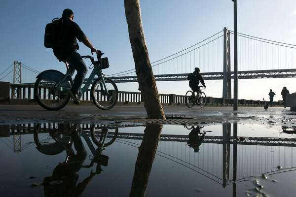 Pedestrians walk and bike past puddles along The Embarcadero that formed during overnight showers, on Wednesday, Nov. 23, 2016 in San Francisco, Calif. The Bay Bridge is seen in the background.