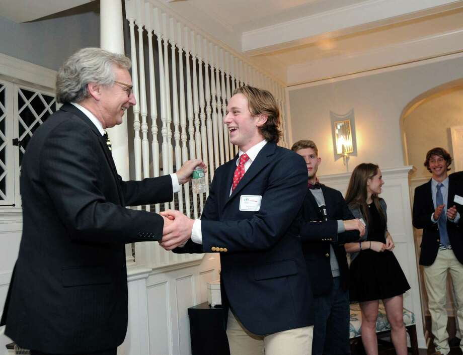 At left, Mark Jaffe, chief executive officer of Children's Learning Centers of Fairfield County, shakes hands with Brunswick School junior Nick Mosher, 17, the president of CLC's 2016 Youth Board during an introduction of the new board at the Mosher residence in the Old Greenwich section of Greenwich. Photo: Bob Luckey Jr. / Hearst Connecticut Media / Greenwich Time