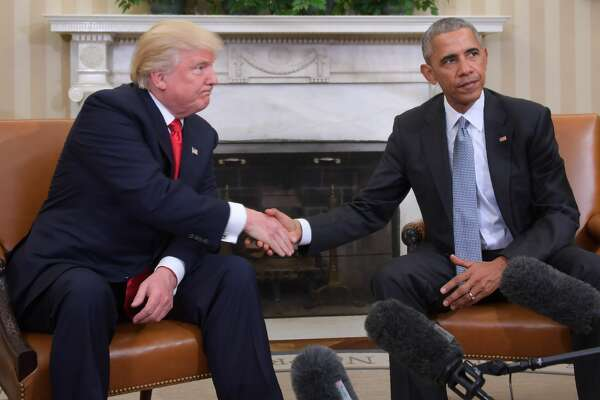 US President Barack Obama and President-elect Donald Trump shake hands during a  transition planning meeting in the Oval Office at the White House on November 10, 2016.