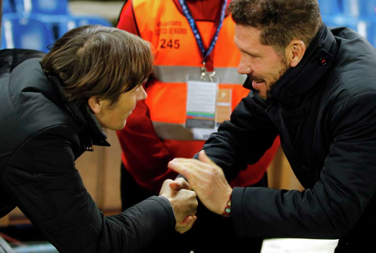 PSV head coach Phillip Cocu, left, shakes hands with Atletico's head coach Diego Simeone during a Champions League, Group D soccer match between Atletico Madrid and PSV Eindhoven at the Vicente Calderon stadium in Madrid, Spain, Wednesday, Nov. 23, 2016. (AP Photo/Paul White)