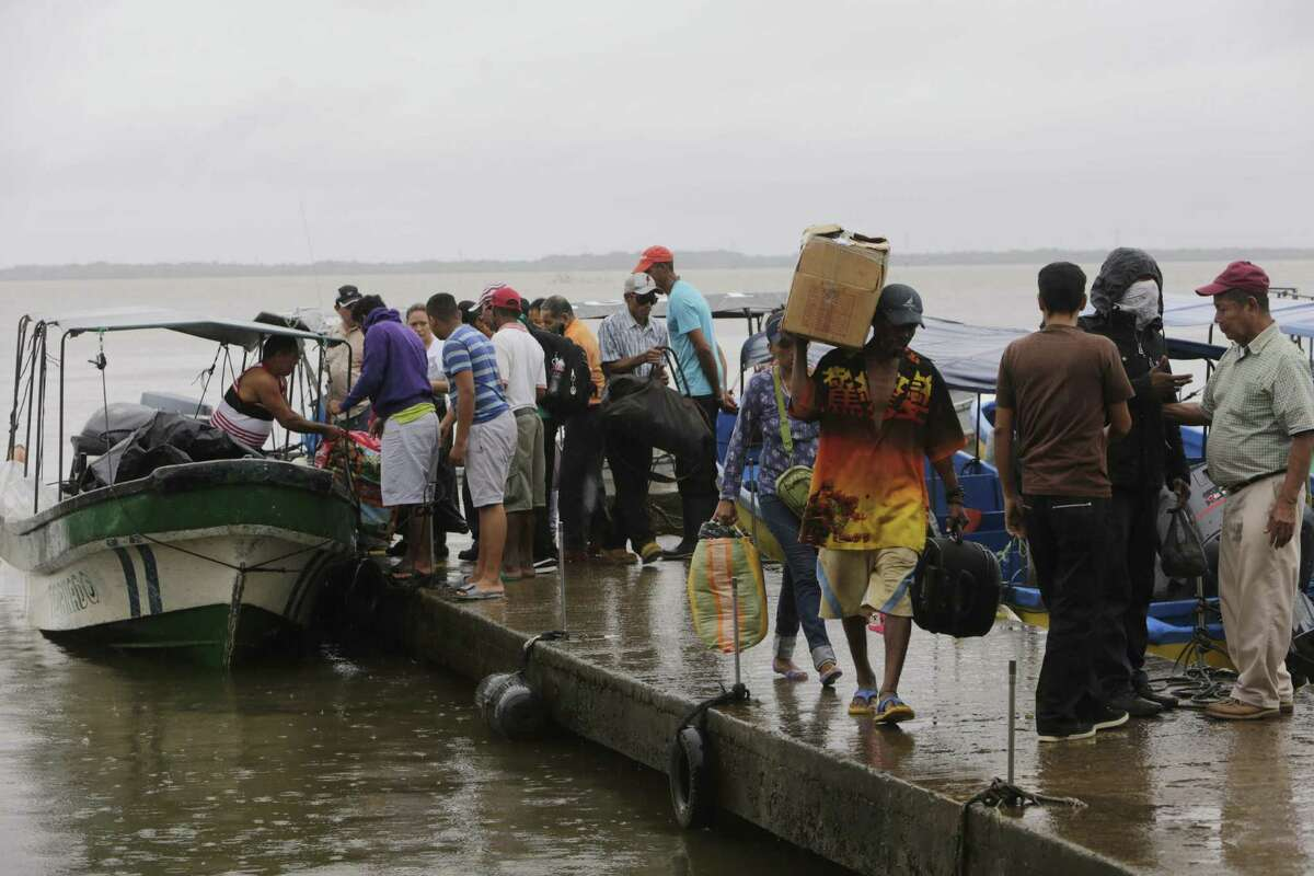 """Residents embark on boats Wednesday to leave before Tropical Storm Otto arrives in Bluefields, Nicaragua. The storm is prompting evacuations ahead of """"life-threatening"""" flooding."""