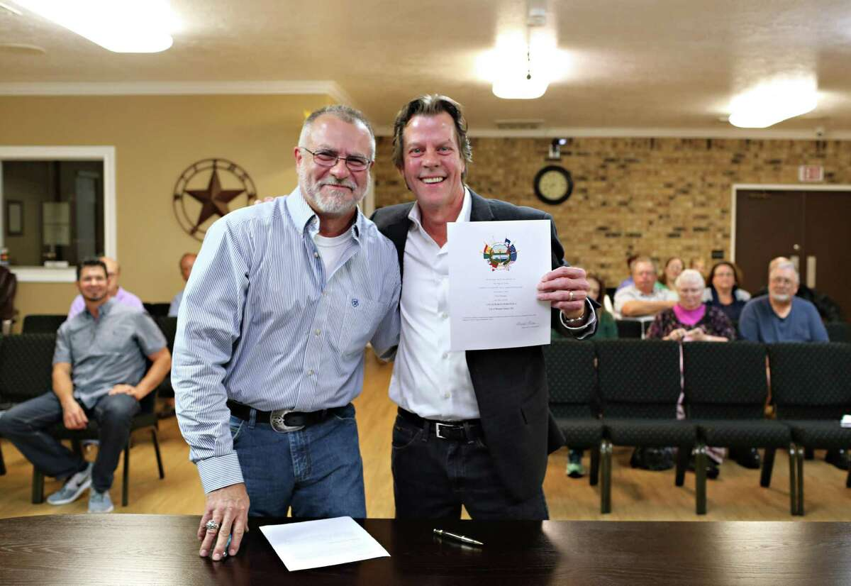 Re-elected Roman Forest council member David Mullane (right) holds his Certificate of Election after being sworn-in to Roman Forest City Council position 3 by Mayor Chris Parr (left) during the regular city council meeting Monday, Nov. 21 at Roman Forest City Hall.