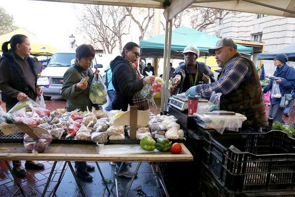 Juanita Kennedy (right wearing white cap) buys vegetables with her food stamp tokens at the Heart of the City Farmer's Market at the civic center on Wednesday, November 23, 2016, in San Francisco, Calif.