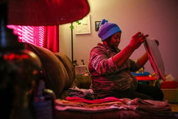 Verna Rankins folds laundry in her apartment in Oakland, California, on Monday, Nov. 21, 2016. Verna is a single parent of a 2-year old boy and is about to start working for Stanford Health insurance.