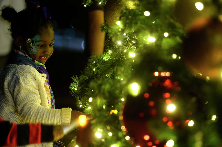 Teryn Holland, 2, looks at the tree during a tree lighting ceremony at Alter's Gem Jewelry on Wednesday evening. This is the store's third year displaying the 36-foot tall tree, which was first displayed for the store's 100th anniversary.  Photo taken Wednesday 11/23/16 Ryan Pelham/The Enterprise Photo: Ryan Pelham / ©2016 The Beaumont Enterprise/Ryan Pelham