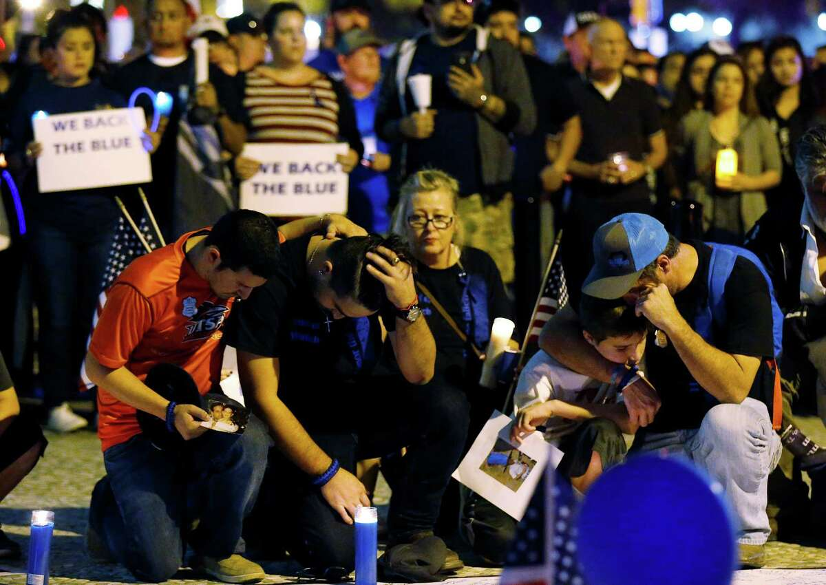 A vigil and march by several hundred law enforcement supporters gathered at the Alamo and marched to San Antonio Police headquarters on Wednesday, Nov. 23, 2016. As the sun waned in the late afternoon sky, candles were lit as people gathered at Alamo Plaza for a
