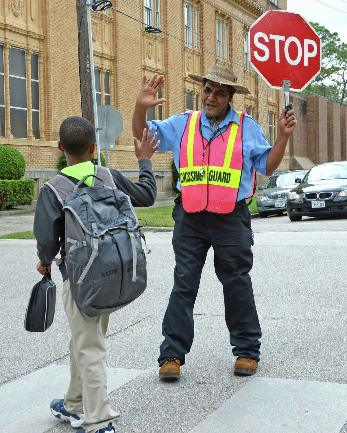 Fetene Yezengaw helps students and parents cross the street in front of Harvard Elementary School in the Heights.