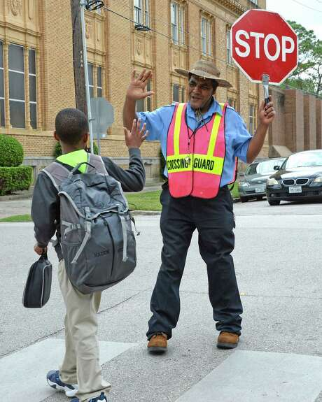 Fetene Yezengaw helps students and parents cross the street in front of Harvard Elementary School in the Heights. Photo: Craig Moseley, Staff / ©2016 Houston Chronicle