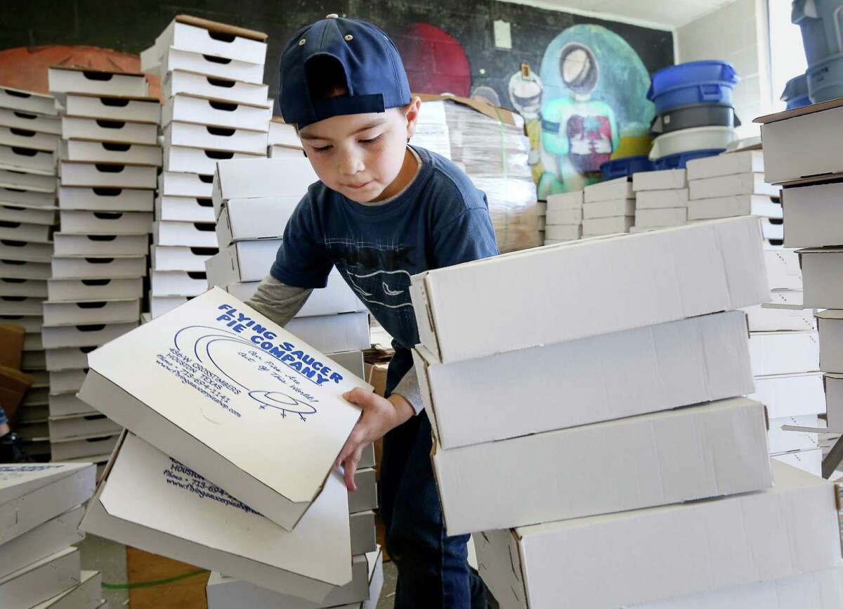 Dominick Fierros, 8, helps build boxes for Thanksgiving pies on Wednesday. Fierros' mother, who works at the pie shop, said her son wanted to help out this year, taking after his sister.