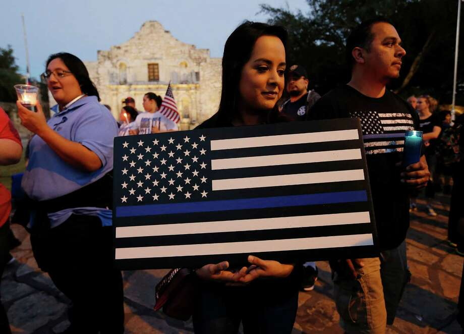 "Ashley Ibarra (center) holds a wooden flag honor fallen police officers as she and her father, John, join a vigil and march by several hundred law enforcement supporters gathered at the Alamo and marched to San Antonio Police headquarters on Wednesday, Nov. 23, 2016. As the sun waned in the late afternoon sky, candles were lit as people gathered at Alamo Plaza for a ""silent"" vigil and march to honor slain SAPD Detective Benjamin Marconi. Members of Marconi's family participated in the march but did not give a statement nor speak at the event. Photo: Kin Man Hui, San Antonio Express-News / ©2016 San Antonio Express-News"