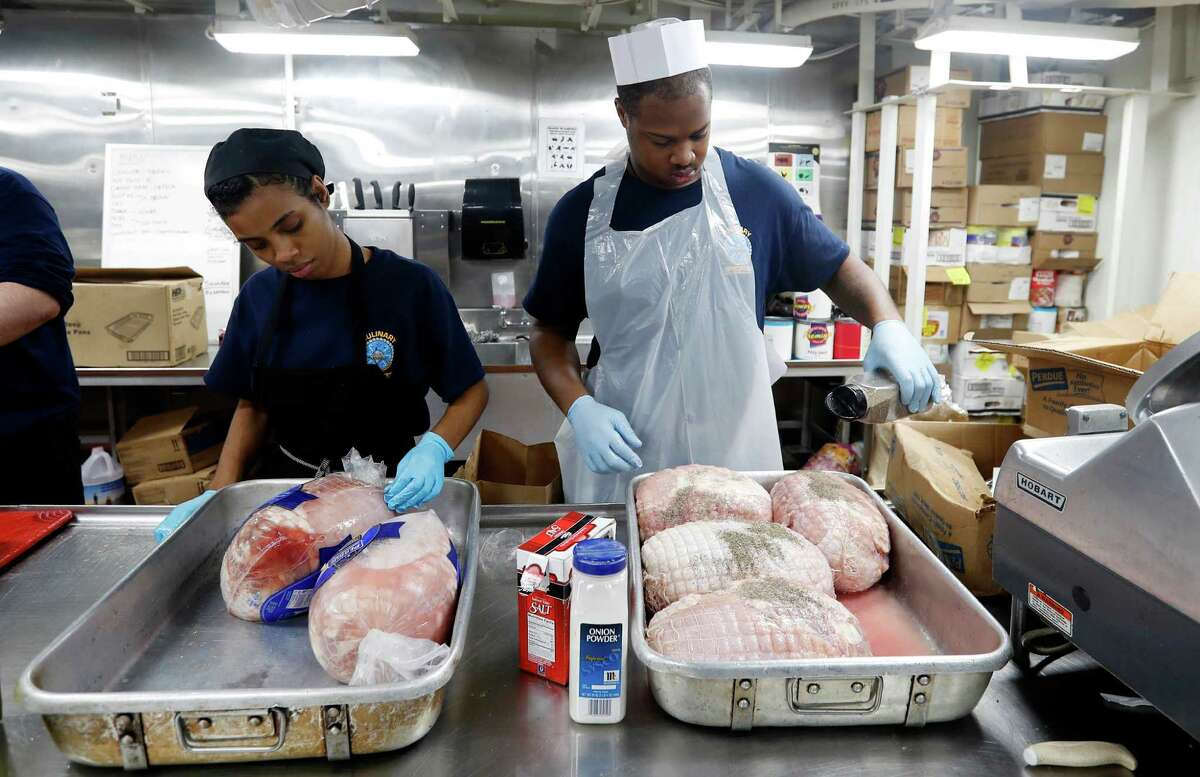 Navy sailors prepare turkeys for a holiday dinner aboard the U.S.S. Dwight D. Eisenhower. The crew is spending their second Thanksgiving on duty.