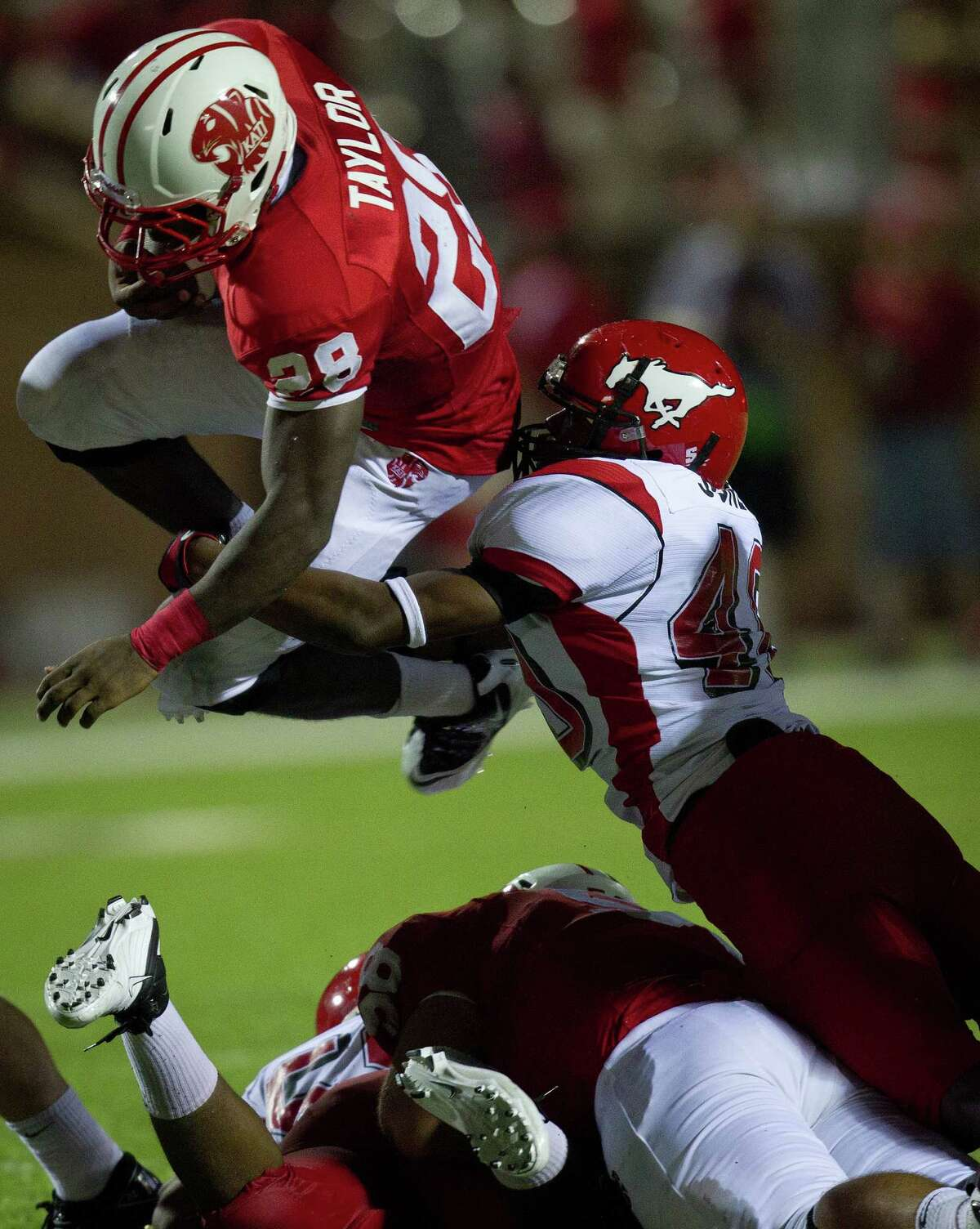 Katy running back Adam Taylor (28) leaps for a first down past North Shore linebacker Ronzel Jones (40) during the third quarter of a high school football game at Rhodes Stadium Friday, Aug. 26, 2011, in Katy. ( Smiley N. Pool / Houston Chronicle )