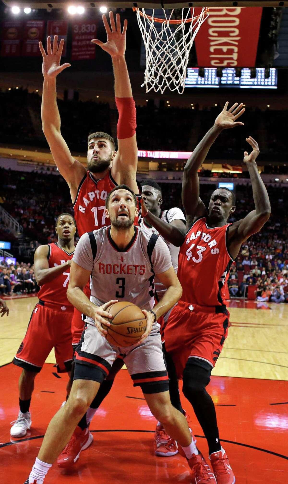 Houston Rockets' Ryan Anderson (3) looks to shoot as Toronto Raptors' Jonas Valanciunas (17) and Pascal Siakam (43) defend during the first quarter of an NBA basketball game Wednesday, Nov. 23, 2016, in Houston. (AP Photo/David J. Phillip)