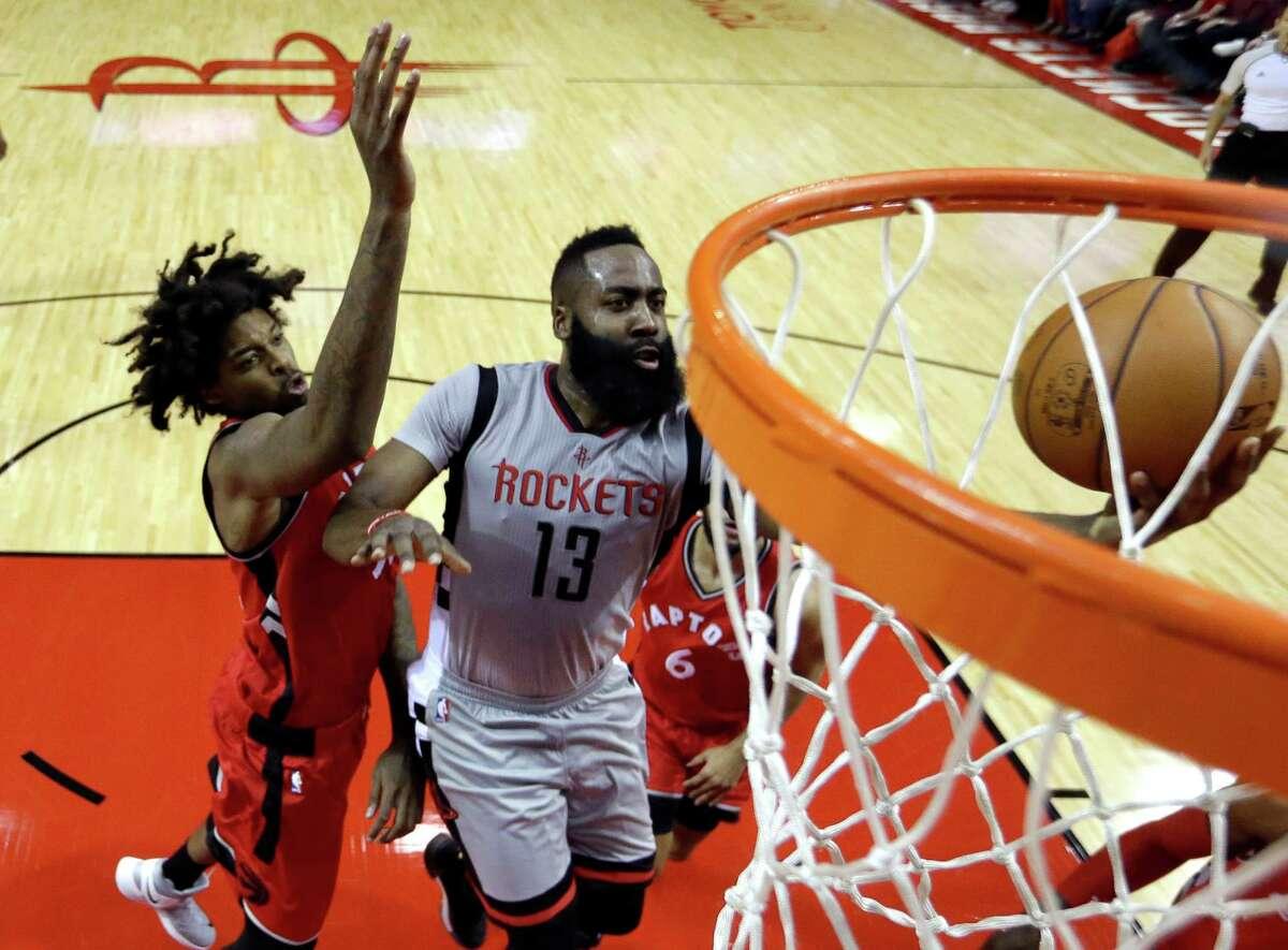 Houston Rockets' James Harden (13) goes up for a shot as Toronto Raptors' Lucas Nogueira, left, defends during the first quarter of an NBA basketball game Wednesday, Nov. 23, 2016, in Houston. (AP Photo/David J. Phillip)