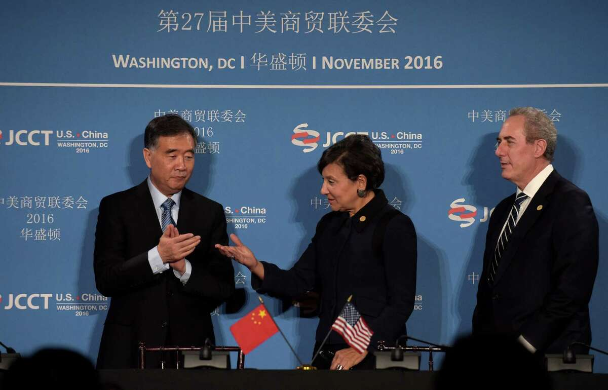 Commerce Secretary Penny Pritzker, center, talks with Chinese Vice Premier of the State Council Wang Yang, left, with U.S. Trade Representative Ambassador Michael Froman at right, following a signing ceremony at the 27th session of the U.S.-China Joint Commission on Commerce and Trade in Washington, Wednesday, Nov. 23, 2016. (AP Photo/Susan Walsh)
