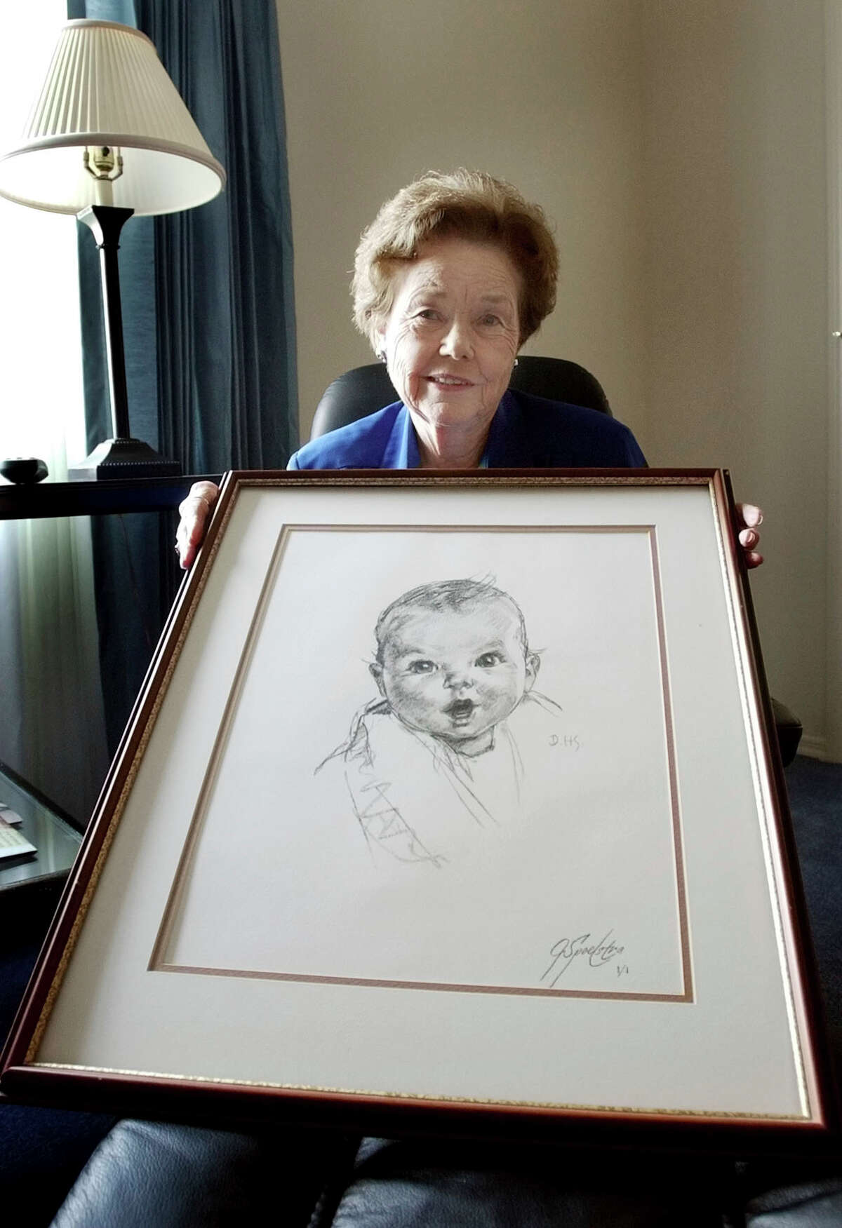 Ann Taylor Cook, shown in 2004, displays a copy of her photo that is used on Gerber baby food products.