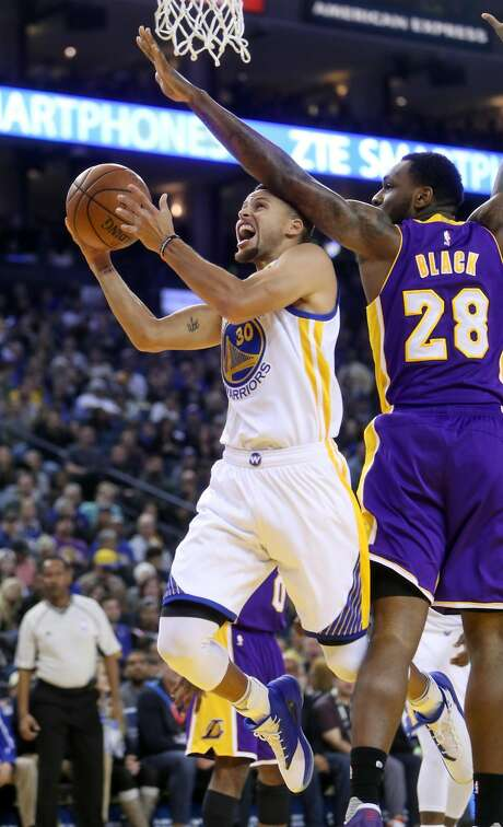 Golden State Warriors' Stephen Curry scores while being fouled by Los Angeles Lakers' Tarik Black in 2nd quarter during NBA game at Oracle Arena in Oakland, Calif., on Wednesday, November 23, 2016. Photo: Scott Strazzante, The Chronicle