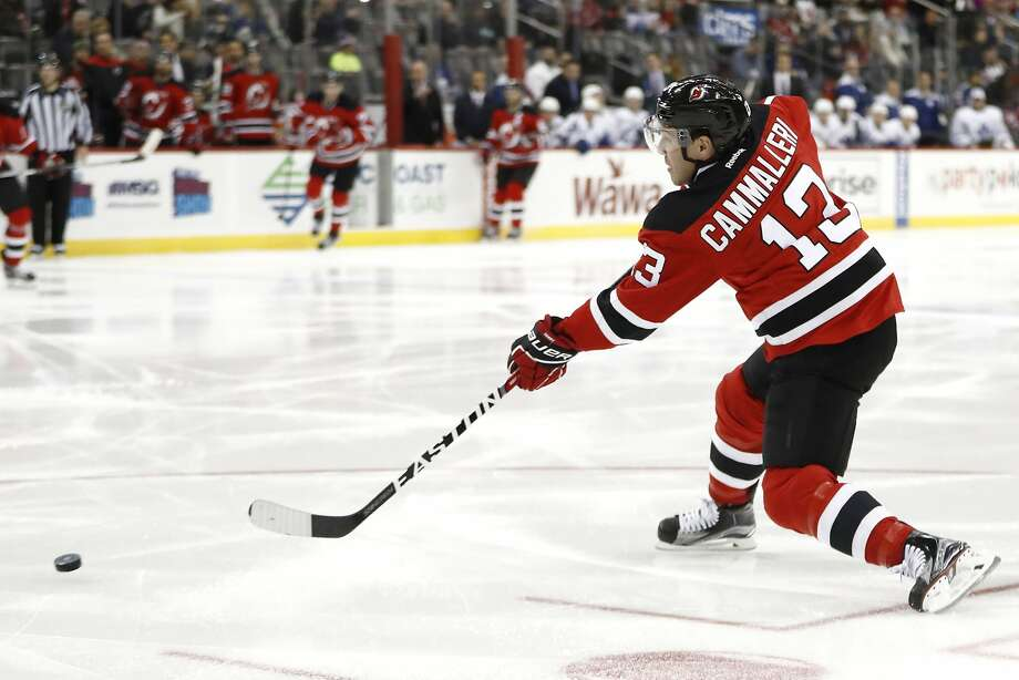 Mike Cammalleri fires a pass that led to a goal by Travis Zajac, one of Cammalleri's three assists in a four-point game. Photo: Julio Cortez, Associated Press