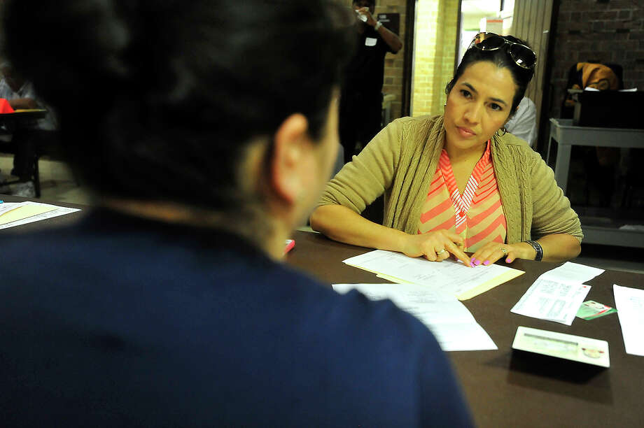 Desiree de la Rosa goes through the intake process with a client as volunteers get to work signing up families in need of assistance with Christmas gifts on the first day of enrollment for the annual Beaumont Enterprise Empty Stocking Fund program at First United Methodist Church in Beaumont.  Photo taken Monday, November 7, 2016 Kim Brent/The Enterprise Photo: Kim Brent / Beaumont Enterprise