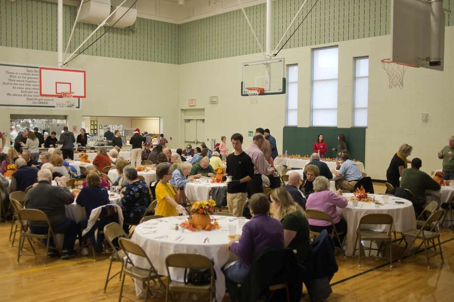 Members of the community enjoy a Thanksgiving meal at St. Brigid Catholic Church during the church's annual Thanksgiving meal. Volunteers started cooking the 18 turkeys Wednesday morning and chefs from The H Hotel carved the turkeys and made gravy and stuffing to go with the meal. Approximately 75 volunteers served 200 meals and any left overs are given to The Open Door and Shelterhouse. Photo: Brittney Lohmiller/Midland Daily News/Brittney Lohmiller