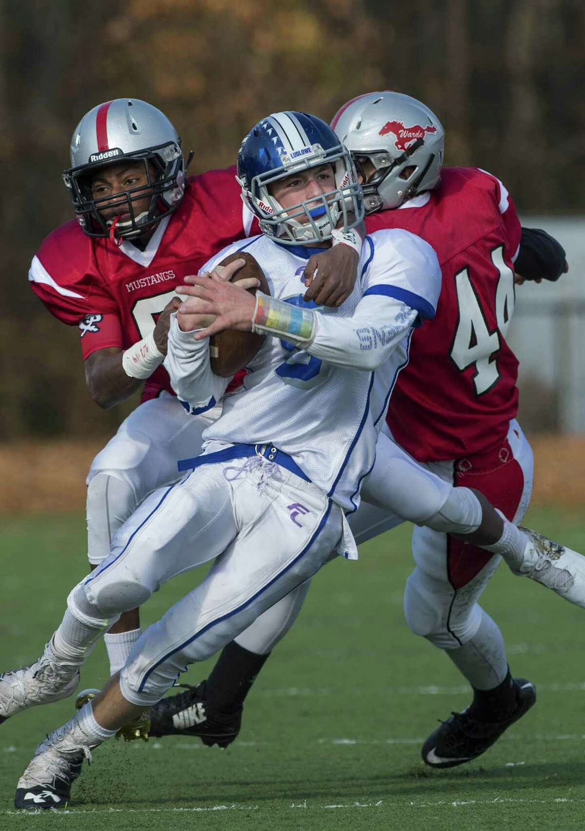 Fairfield Warde High School?'s Hank Jean-Jacques and Joe Gjinaj tackle Fairfield Ludlowe High School?'s Brian Howell during their annual Thanksgiving Day football game played at Fairfield Warde High School, Fairfield, CT Thursday, November 24, 2016.