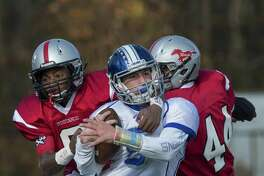 Fairfield Warde High School's Hank Jean-Jacques and Joe Gjinaj tackle Fairfield Ludlowe High School's Brian Howell during their annual Thanksgiving Day football game played at Fairfield Warde High School, Fairfield, CT Thursday, November 24, 2016.