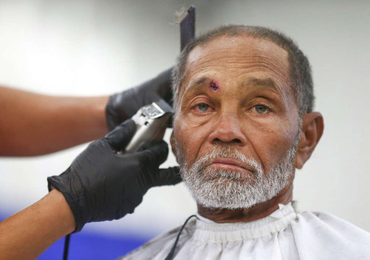 John Vaughn, who stays in the Third Ward neighborhood, gets a haircut at the 38th Annual Thanksgiving Big Super Feast at the George R. Brown Convention Center on Nov. 24 in Houston.