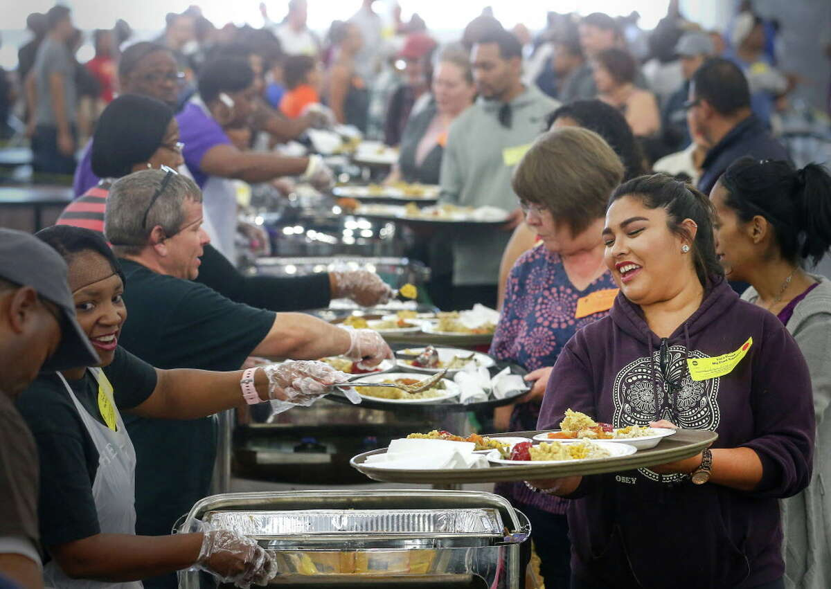 Chasya Rodriguez, a volunteer at the 38th Annual Thanksgiving Big Super Feast, smiles as she goes through the line with a tray of food for a group of three, at the George R. Brown Convention Center on Nov. 24 in Houston.