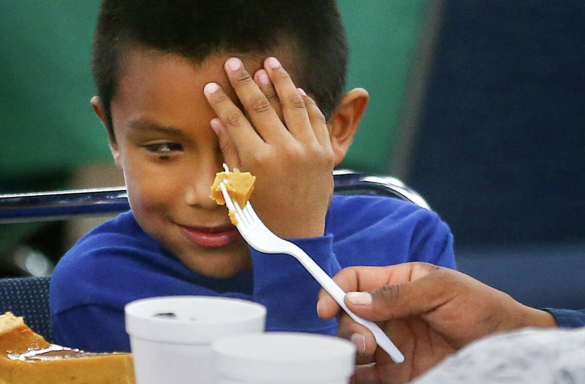 Miguel Munoz, 8, hides his face from a piece of pumpkin pie that his dad is holding, at the 38th Annual Thanksgiving Super Feast at the George R. Brown Convention Center on Nov. 24 in Houston.