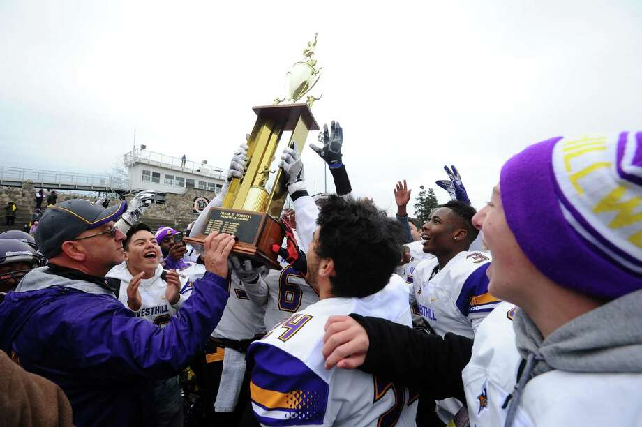 Westhill players and coaches lift the Robotti trophy after defeating Stamford High School 29-6 at Stamford High's Boyle Stadium in Stamford, Conn. on Thursday, Nov. 24, 2016. Photo: Michael Cummo / Hearst Connecticut Media / Stamford Advocate