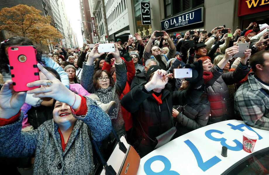 People crowd a New York City Police cruiser to get a photograph of Santa Claus during the Macy's Thanksgiving Day parade, Thursday, Nov. 24, 2016, in New York. (AP Photo/Julio Cortez) Photo: Julio Cortez, Associated Press / Copyright 2016 The Associated Press. All rights reserved.