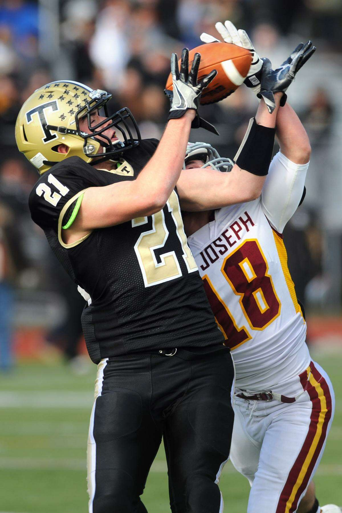 Trumbull?'s Peter Raverta makes a reception ahead of St. Joseph defender Connor Murphy during high school football action at Trumbull High School on Thanksgiving Day, Nov. 24, 2016.