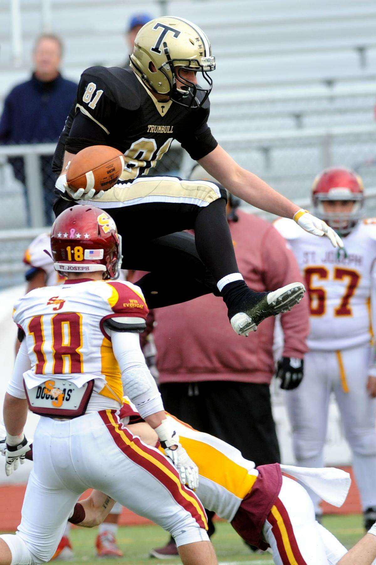 Trumbull receiver Zachary Lombardi leaps over St. Joseph defenders during high school football action at Trumbull High School on Thanksgiving Day, Nov. 24, 2016.