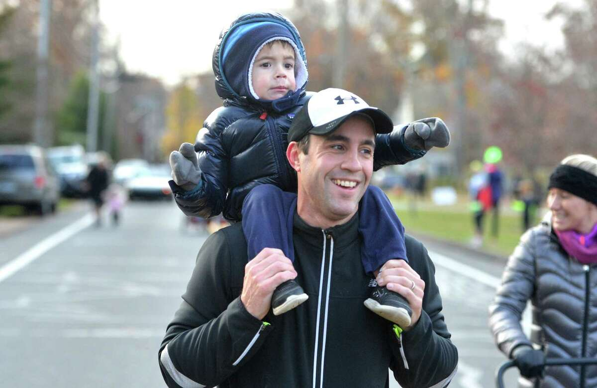 Stephen Pearce heads to the 1 mile finish line with 3yr old son Jack on his shoulders during the annual Rowayton Turkey Trot held on Thanksgiving morning to raise funds for the Rowayton Arts Center, the Rowayton Gardeners and the Rowayton Volunteer Fire Department. on Thursday November 24, 2016 in Norwalk Conn