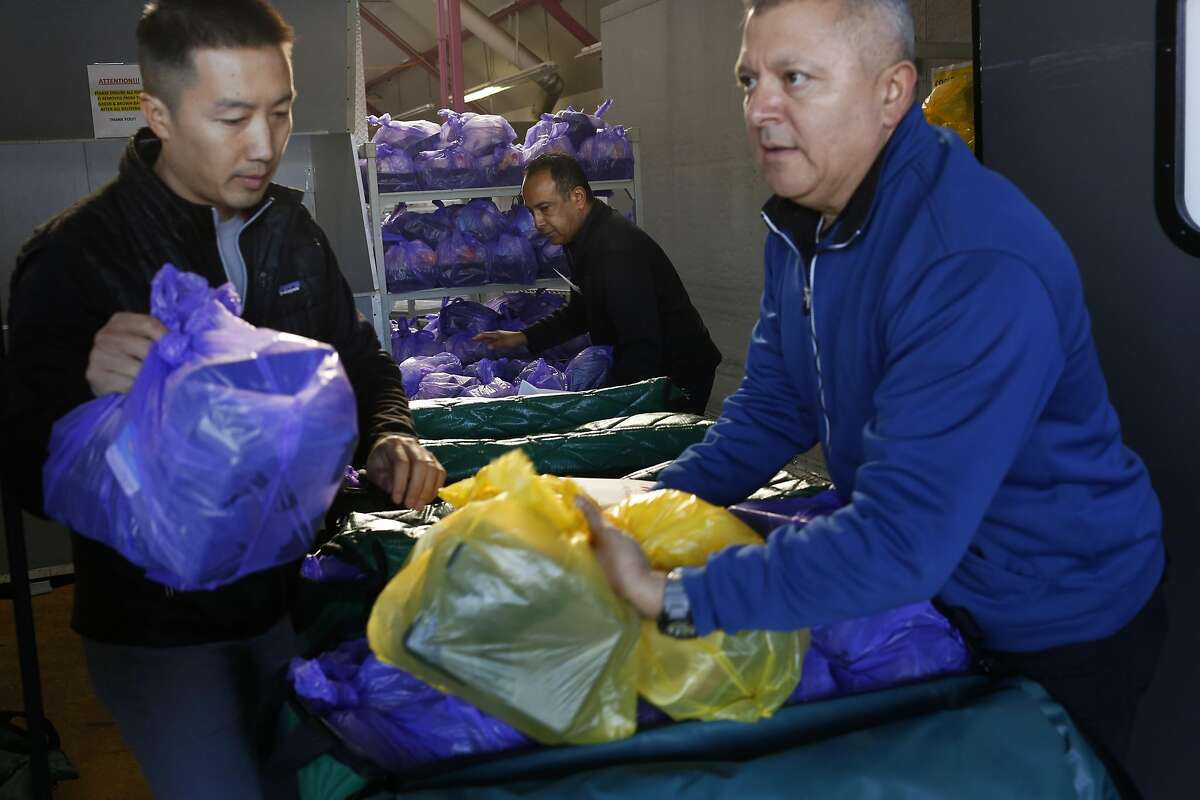 Volunteer Lawrence Leung, left, helps load Thanksgiving meals for delivery with employees Gustavo Lopez, right, and Philip Duarte from Meals on Wheels Nov. 24, 2016 in San Francisco, Calif.