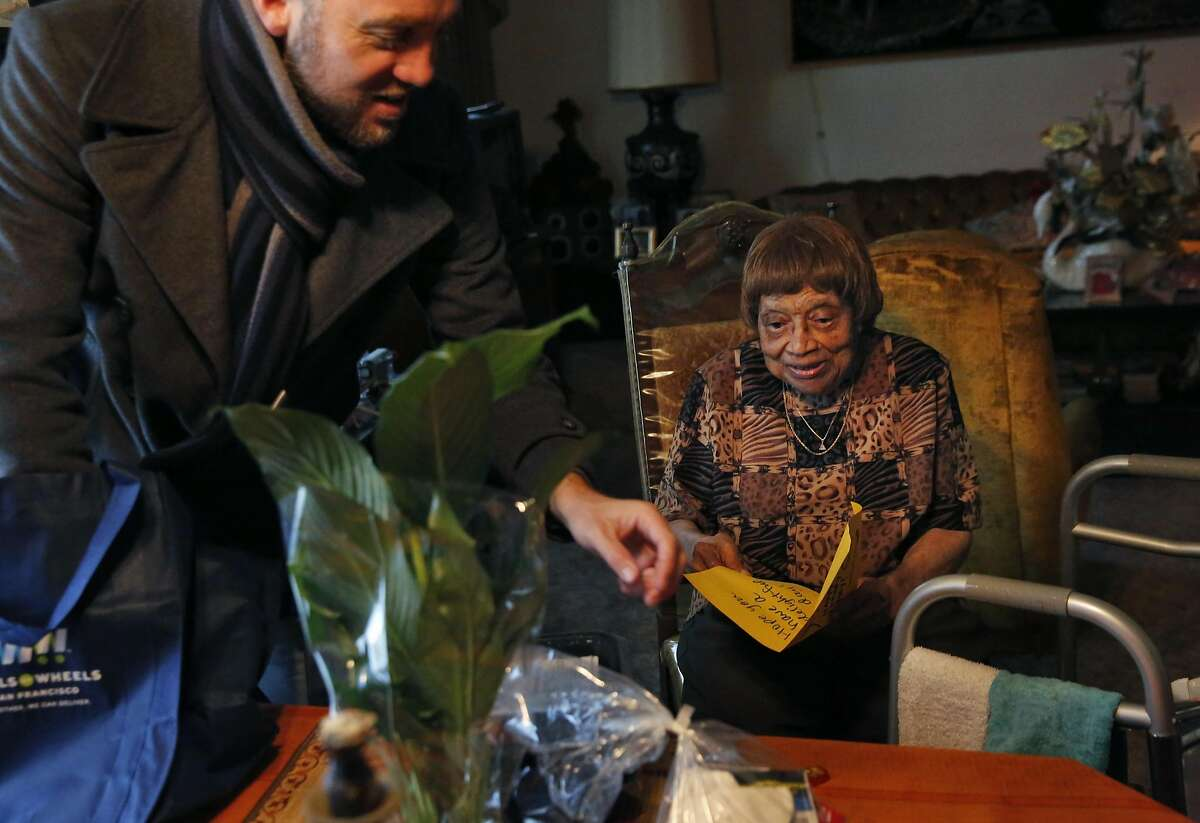Maggie Agee, 90, looks over her food and gift bag delivery from Karl Robillard from Meals on Wheels in her home Nov. 24, 2016 in San Francisco, Calif.