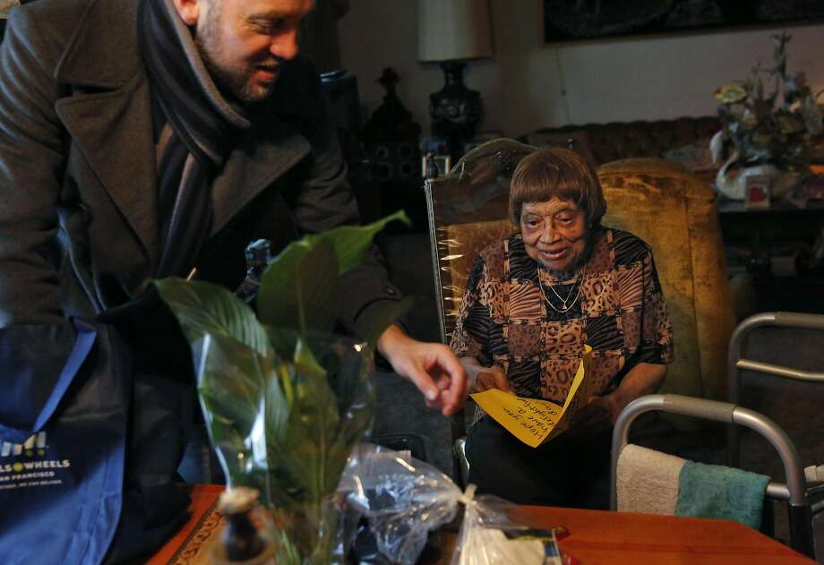 Above: Karl Robillard of Meals on Wheels delivers a Thanksgiving meal and gift bag to Maggie Agee, 90. Photo: Leah Millis, The Chronicle