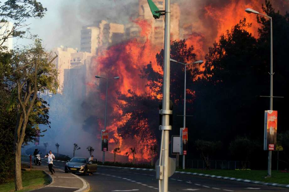 People run as wildfires rages in Haifa, Israel, Thursday, Nov. 24, 2016. A raging wildfire ripped through parts of Israel's third-largest city on Thursday, forcing tens of thousands of people to evacuate their homes and prompting a rare call-up of hundreds of military reservists to join overstretched police and firefighters. Spreading quickly due to dry, windy weather, the fire quickly spread through Haifa's northern neighborhoods. While there were no serious injuries, several dozen people were hospitalized for smoke inhalation. (AP Photo/Ariel Schalit) Photo: Ariel Schalit, STF / Copyright 2016 The Associated Press. All rights reserved.