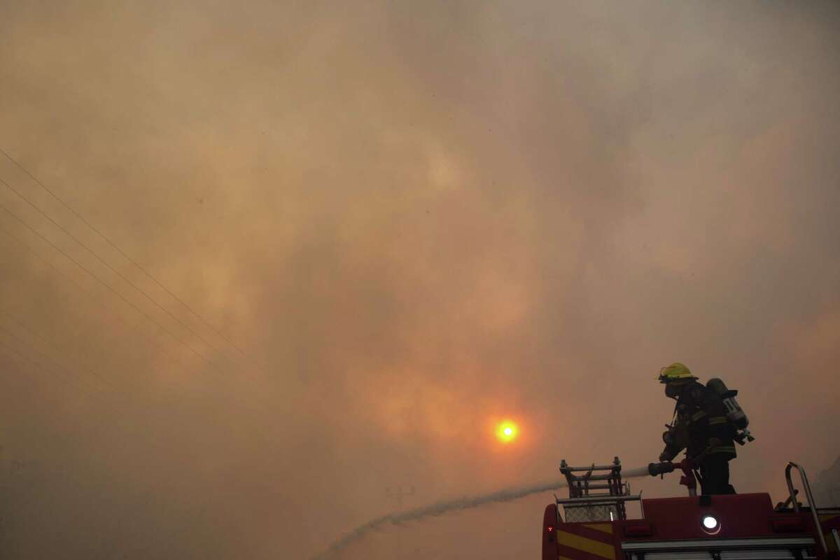 A Firefighter works at the site of wildfires in Haifa, Israel, Thursday, Nov. 24, 2016. A raging wildfire ripped through parts of Israel's third-largest city on Thursday, forcing tens of thousands of people to evacuate their homes and prompting a rare call-up of hundreds of military reservists to join overstretched police and firefighters. Spreading quickly due to dry, windy weather, the fire quickly spread through Haifa's northern neighborhoods. While there were no serious injuries, several dozen people were hospitalized for smoke inhalation. (AP Photo/Ariel Schalit)