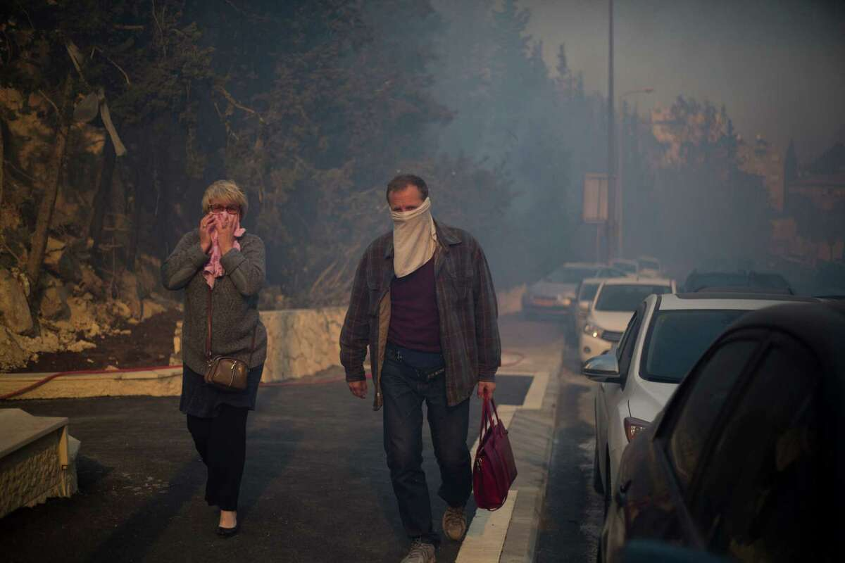 People walk a away from wildfires in Haifa, Israel, Thursday, Nov. 24, 2016. A raging wildfire ripped through parts of Israel's third-largest city on Thursday, forcing tens of thousands of people to evacuate their homes and prompting a rare call-up of hundreds of military reservists to join overstretched police and firefighters. Spreading quickly due to dry, windy weather, the fire quickly spread through Haifa's northern neighborhoods. While there were no serious injuries, several dozen people were hospitalized for smoke inhalation. (AP Photo/Ariel Schalit)