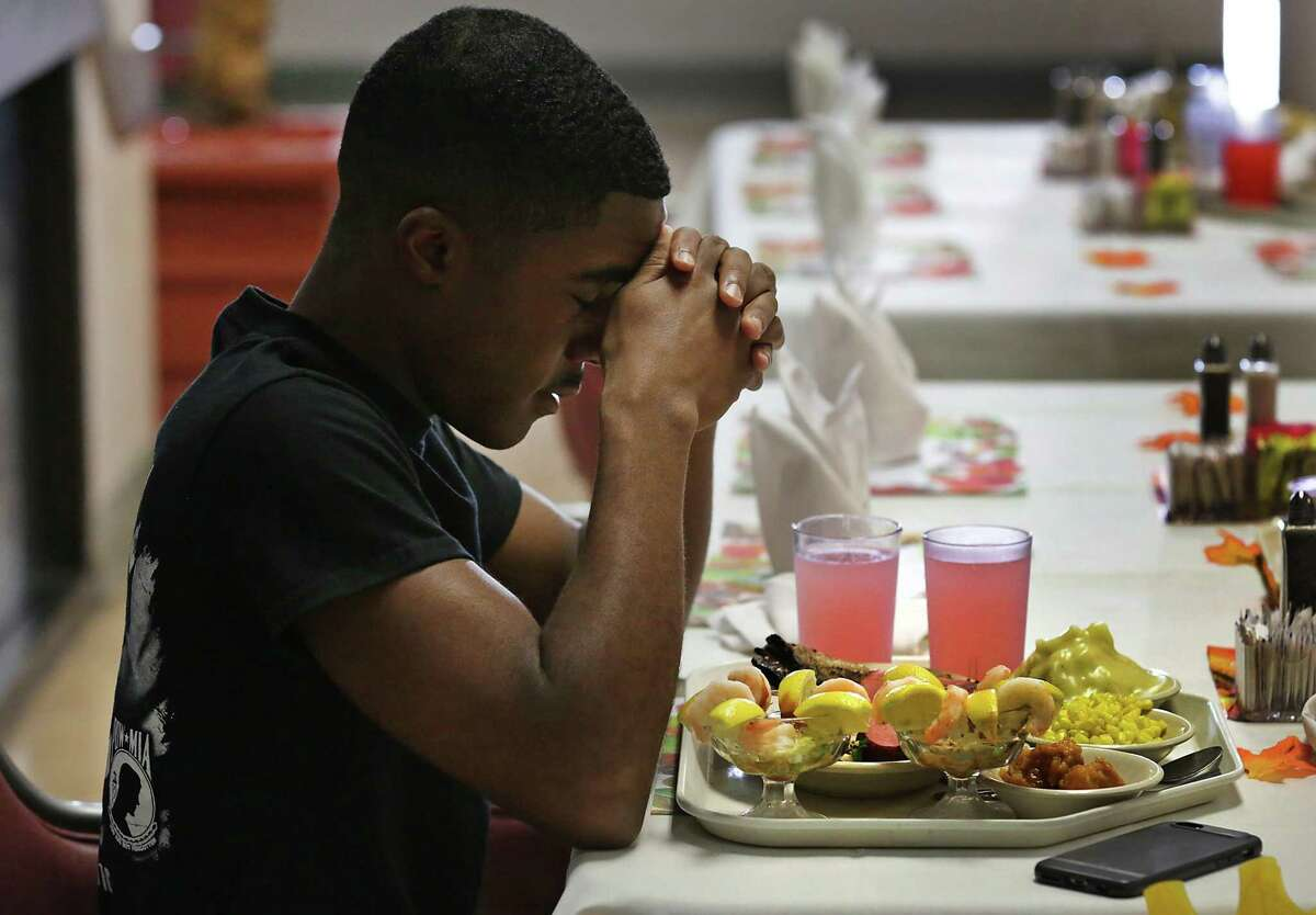 Airman Jahshawnte Coates from the Bronx, New York City, bows his head in prayer before digging into his Thanksgiving dinner in a dining hall at Joint Base San Antonio-Lackland in 2016.