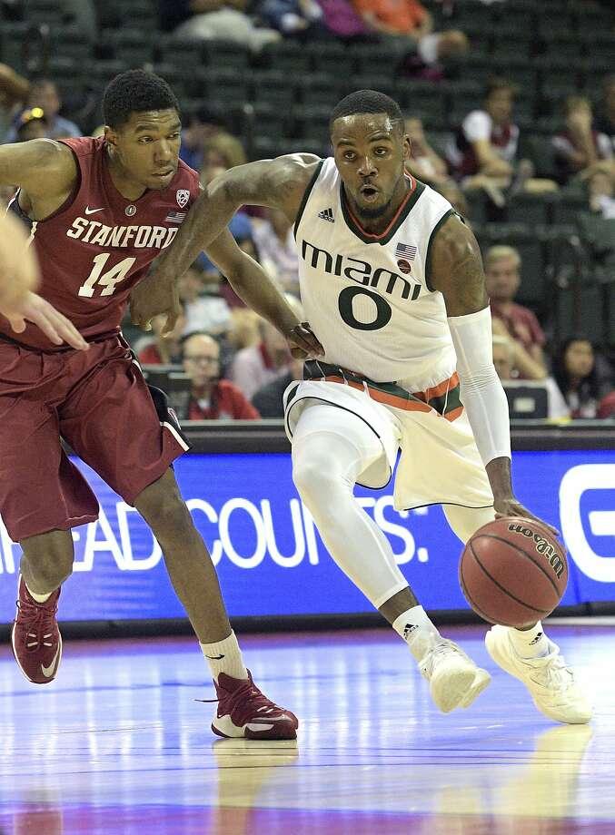 Ja'Quan Newton, who led Miami with 20 points, drives past Stanford guard Marcus Sheffield. Photo: Phelan M. Ebenhack, Associated Press